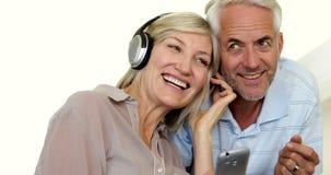 一起听到音乐的逗人喜爱的成熟夫妇 影视素材