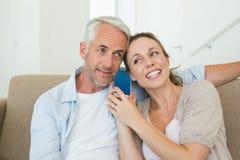 一起听电话的愉快的夫妇在长沙发 库存照片