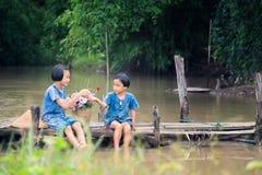 一起和演奏水的两个女孩孩子坐在沼泽,演奏水的亚洲孩子的木桥 库存图片