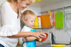 一起哄骗男孩和母亲洗涤的盘-获得乐趣在厨房 免版税库存照片