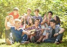 一起唱歌与吉他的小组愉快的青年人 免版税库存图片