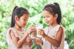 一起喝从玻璃的两个逗人喜爱的亚裔儿童女孩牛奶 库存照片