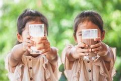 一起喝从玻璃的两个逗人喜爱的亚裔儿童女孩牛奶 免版税库存图片