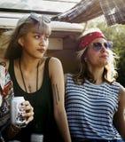 一起喝酒精啤酒的朋友在旅行旅途上 库存照片