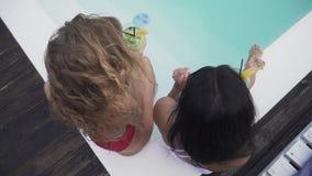 一起喝coctails的两个亭亭玉立的俏丽的女孩和有美好时光在休息室 泳装的两个女朋友 影视素材