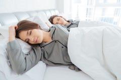 一起在和睡觉在床上的两姐妹孪生 免版税库存图片