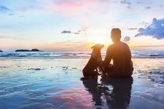 一起坐友谊概念、的人和的狗 免版税库存图片
