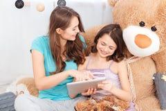 一起坐和使用片剂的两个快乐的逗人喜爱的姐妹 免版税库存图片