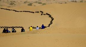 一起坐在一片沙漠的小组年轻朋友在迪拜,阿拉伯联合酋长国 库存图片