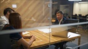 一起坐在书桌和看人的愉快的年轻夫妇坐在他们前面和拿着合同 影视素材