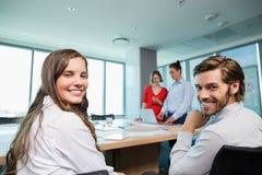 一起坐在会议室的微笑的商业主管 免版税图库摄影