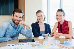 一起坐在会议室的微笑的商业主管 库存照片
