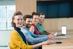 一起坐在会议室的微笑的商业主管 免版税库存照片