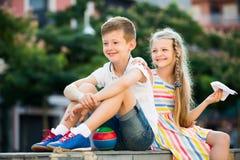 一起坐在公园的微笑的女孩和男孩 免版税库存照片