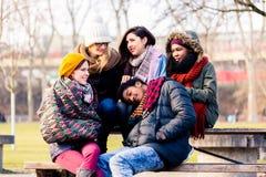 一起坐在公园的美丽的青年人 库存图片