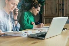 一起坐在办公室的两个年轻女商人在桌和工作上 在桌膝上型计算机和纸图 库存图片