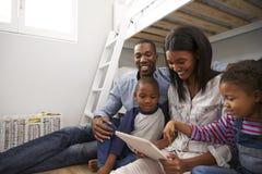 一起坐在卧室的家庭使用数字式片剂 免版税库存照片
