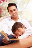 一起坐在庭院阅读书的父亲和儿子 库存图片