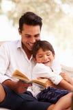 一起坐在庭院阅读书的父亲和儿子 库存照片