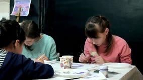 一起坐在教室和画的桌附近的儿童男孩和女孩 他们是他们的年轻人和 股票录像
