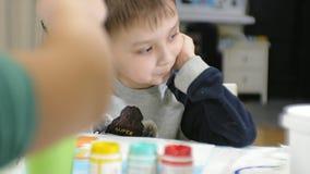 一起坐在教室和画的桌附近的儿童男孩和女孩 他们是他们的年轻人和 股票视频