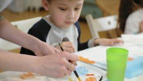 一起坐在教室和画的桌附近的儿童男孩和女孩 他们是他们的年轻人和 影视素材