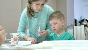 一起坐在教室和画的桌附近的儿童男孩 他们是他们的年轻和美丽的老师 股票视频