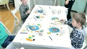 一起坐在教室和画的桌附近的儿童男孩 他们是他们的年轻和美丽的老师 影视素材