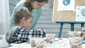 一起坐在教室和画的桌附近的儿童男孩 他们是他们的年轻和美丽的老师 股票录像