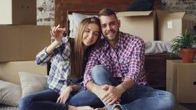 一起坐在新房里,把握关键和看与纸盒箱子的已婚夫妇画象照相机 股票录像