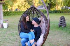 一起坐在暂停的椅子的男孩和女孩,拥抱每个o 图库摄影