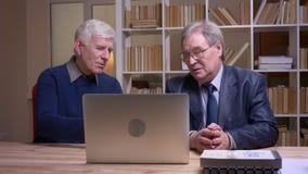 一起坐在桌上的老商人画象与膝上型计算机一起使用和严重谈论项目 影视素材