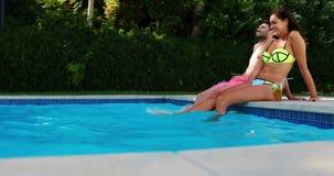 一起坐在游泳池边的微笑的夫妇 影视素材