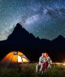一起坐在营火附近的两个恋人远足者和在晚上发光阵营在星下和看对满天星斗的天空 库存照片