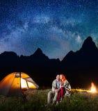 一起坐在营火附近的愉快的夫妇游人和在晚上发光阵营在星下和看对满天星斗的天空 图库摄影