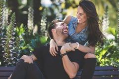 一起坐外部的笑的夫妇获得乐趣 库存图片