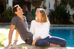一起坐外面由水池的笑的夫妇 免版税图库摄影