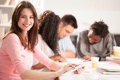 一起坐微笑的大学生 免版税库存图片