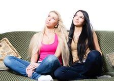 一起坐二个相当年轻的女朋友或的姐妹画象  免版税库存图片