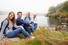 一起坐由湖的一对资深和一对年轻成人夫妇 库存照片