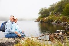 一起坐由湖的资深夫妇,看对照相机 库存图片