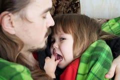 一起基于扶手椅子的父亲和孩子 闩上构成概念系列螺母 愉快的父母身分,父权 在毯子和女儿包裹的爸爸 免版税库存照片