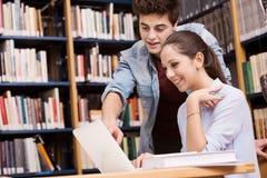 一起学习在图书馆的同学 免版税库存图片