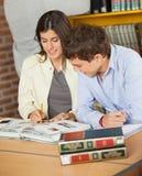 一起学习在图书馆的学院朋友 库存照片