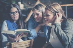 一起学习在图书馆里的三个学生女孩 免版税图库摄影