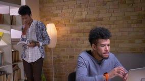 一起学习在大学图书馆里的两名种族地不同的学生特写镜头射击  非裔美国人男性使用 股票录像