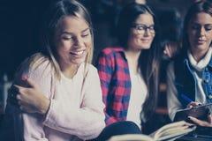 一起学会三个学生的女孩坐在图书馆里和 库存照片
