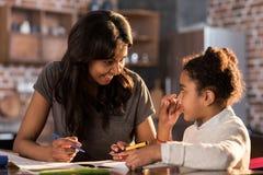 一起学会和做家庭作业,家庭作业帮助概念的母亲和女儿 库存照片