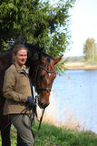 一起少妇和棕色马在河海岸 免版税库存图片