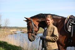 一起少妇和棕色马在河海岸 免版税库存照片